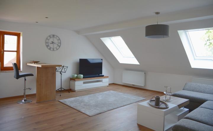 Einblick in das Wohnzimmer eines von der Zimmerei Steinberger ausgebauten Dachgeschosses. Es ist ein Sofa, der Fernseher und ein Baartisch mit Hocker und Wanduhr zu sehen. In der Dachschräge befinden sich zwei ins Grüne zeigende Dachfenster
