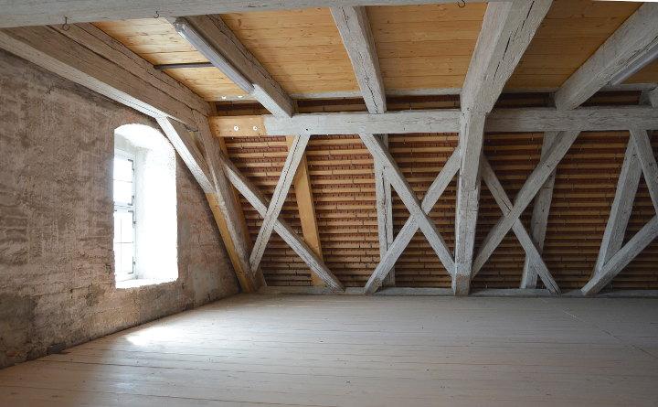 Dachboden eines alten Pfarrgebäudes mit historischen und neuen Holzbalken und einem seitlichen Fesnster