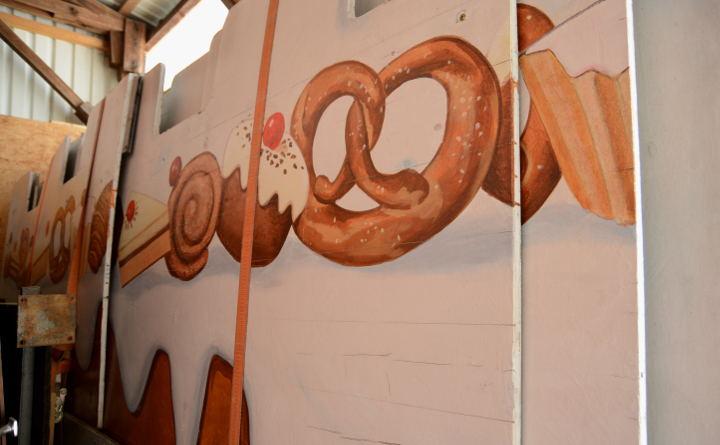 Gelagerte Teile eines Volksfeststandes. Darauf gemalt sind Backwaren.