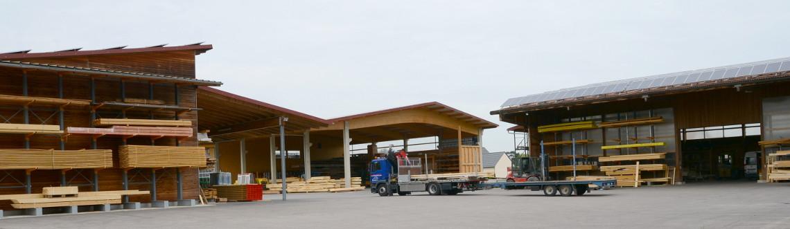 Ausschnitt des Betriebsgeländes der Zimmerei in Nötting. Es sind Lagerhallen, ein Lastwagen und die Abbundhalle zu sehen