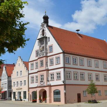 Altes Rathaus in Geisenfeld. Rosa- weißes Barockgebäude mit Stuckfigur an der Fassade