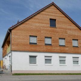 Wohnhaus mit Aufstockung, die mit Holz eingekleidet ist