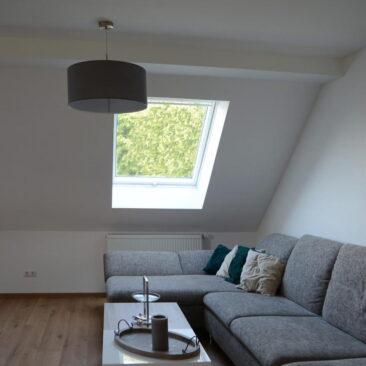 Innenansicht eines durch die Zimmerei ausgebauten Dachstuhls mit Dachfenster. Einblick in ein Wohnzimmer