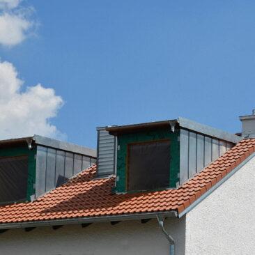 Aussenansicht eines Daches mit neuen Dachgauben vor blauem Himmel