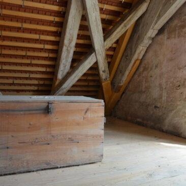 Dachboden. Eine große Holzkiste steht vor im Hintergrund sichtbarer neuer Dachlattung verknüpft mit alten Balken