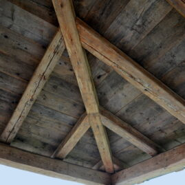 Detail einer Terrassenüberdachung mit Balken aus Altholz.