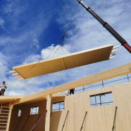 Kran hebt Fertigteil eines Holzhauses in die Luft