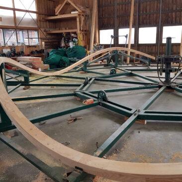 Unterbau eines historischen Kinderkarusells. Geschwungene Holzbalken werden kreisförmig in der Zimmerei Steinberger zusammengefügt.