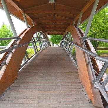 Bild einer Fußgängerbrücke aus Holz und Metall über die Paar in Rechertshofen. Sonderbau der Zimmerei Steinberger