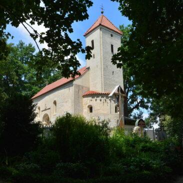Kleine Kirche aus Sandstein umrahmt von Blättern