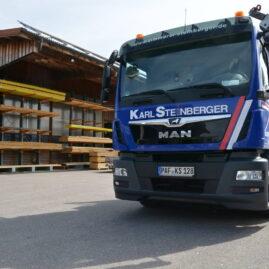 Blauer Lastwagen mit weißem Schriftzug Karl Steinberger. Im Hintergrund Ausschnitt des Werksgeländes zu sehen
