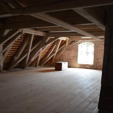 Bild eines Dachbodens. Neu gezimmertes Gebälk verknüpft mit Altem.