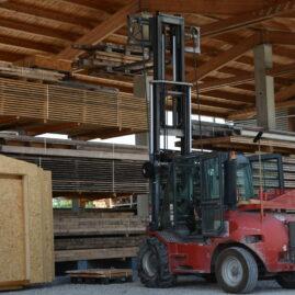 Seitenansicht eines Staplers der gerade Holzpalääten in Lagerhalle lädt