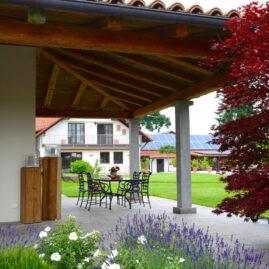 Überdachung einer Terrasse aus Altholz. Im Vordergrund blüht Lavendek umrahmt von Japanischem Ahorn