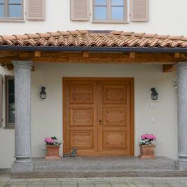 Eingangsbereich einer Toskanavilla. Vordach ruht auf Altholzbalken.