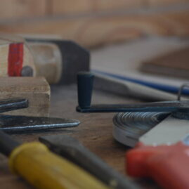 Maßband, Hobel und Zimmererhammer in Detailaufnahme auf Werkbank
