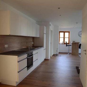 Weiße glänzende Küchenzeile. Im Hintergrund ein kleiner Esstisch am Holzfenster