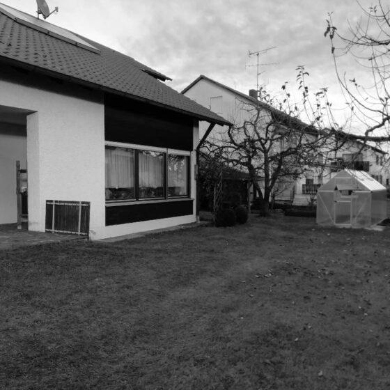 Ansicht eines Bungalows mit rasenfläche und Gewächshaus vor der Aufstockung