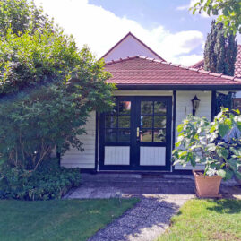 Ein Gartenhaus mit großer gläsernen Flügeltür und weisser Holzverkleidung. Das Dach ist mit roten Ziegeln gedeckt