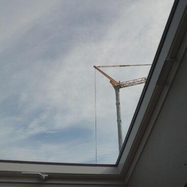 Detailansicht eines Dachfensters im Rohbau einer Aufstockung mit Kran am Himmel