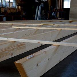 Holzbalken auf dem Boden der Abbundhalle der Zimmerei