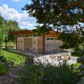Ein wunderschönes Gartenhaus aus Holz mit 3 Türen und schmalen Fenstern umrahmt von Lavendel, Kiefern und Natursteinen