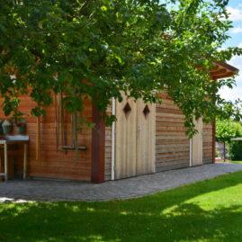 Seitenansicht des Gartenhauses. Gartenwerkzeug hängt geordnet an der Wand. Ein Apfelbaum rahmt das Gartenhaus ein.