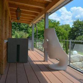 Blick auf die Terrasse des Gartenhauses. Ein Stuhl weisser Stuhl in Form eines Gesichts und eine marrokkanische Lampe bilden Mittelpunkt des Bildes